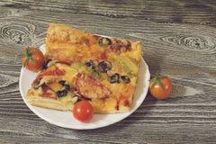 Pizza con la salchicha, las aceitunas, los tomates y el queso Foto de archivo