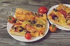 Pizza con la salchicha, las aceitunas, los tomates y el queso Imagenes de archivo