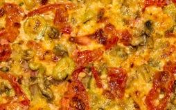 Pizza con la salsiccia, i pomodori, i funghi ed il formaggio Fondo fotografia stock