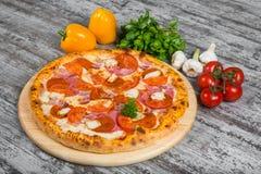 Pizza con la salsiccia, pollo, bacon, prosciutto, con i rosmarini e le spezie immagini stock libere da diritti