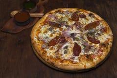 Pizza con la ternera, el jamón, el queso y tomates secados al sol imagen de archivo
