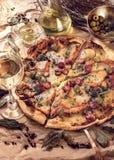 Pizza con las salchichas, el jamón y las aceitunas Cerca del aceite de oliva y del vino blanco imágenes de archivo libres de regalías