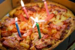Pizza con las velas para celebrar un cumpleaños Imagen de archivo