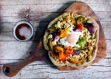 Pizza con las verduras de raíz, el requesón, el huevo y las flores Foto de archivo
