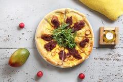 Pizza con las verduras y la salsa de tomate con las hojas del cohete foto de archivo