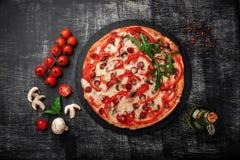 Pizza con le salsiccie affumicate, il formaggio, i funghi, i pomodori ciliegia, i peperoni dolci ed i verdi su una pietra fotografia stock libera da diritti