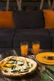 Pizza con los huevos, los platos y el jugo en la tabla contra la perspectiva del sofá azul Imagen de archivo