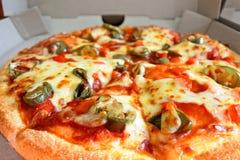 Pizza con los jalapenos que rematan en caja de la entrega de la cartulina Fotografía de archivo libre de regalías