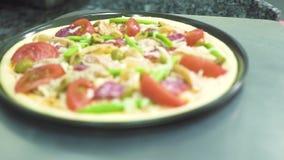 Pizza con los salchichones y los tomates en la pala de la cocina para cocer en horno en restaurante Comida que cocina concepto pr almacen de metraje de vídeo