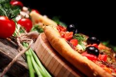 Pizza con los tomates, el queso de la mozzarella, las aceitunas negras y la albahaca Fotos de archivo