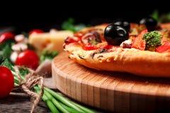 Pizza con los tomates, el queso de la mozzarella, las aceitunas negras y la albahaca Fotografía de archivo