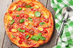 Pizza con los tomates, la mozzarella y la albahaca Imagen de archivo libre de regalías
