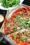 Pizza con proscuitto, los tomates y el arugula Foto de archivo libre de regalías