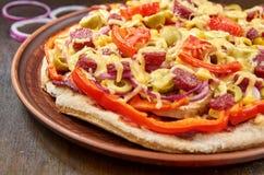 Pizza con salame, i pomodori, il peperone dolce, la cipolla, le olive verdi, il mais, il formaggio e le spezie su fondo di legno  Immagini Stock Libere da Diritti