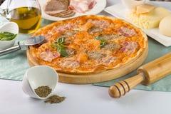 Pizza con tocino y tomates en la placa de madera Imagen de archivo libre de regalías