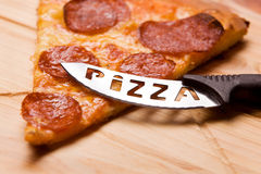 Pizza con un pizza-coltello Fotografie Stock