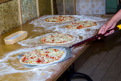 Pizza cooking. focus on medium pizza Stock Photography