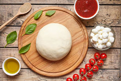 Pizza cooking ingredients on cutting board. Dough, mozzarella, tomatoes, basil, olive oil, spices. Work with the dough. Pizza cooking ingredients on cutting Stock Images