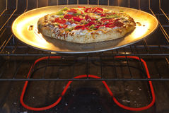 Pizza cooking in an oven Stock Photo