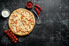 Pizza cortada com tomates de cereja, anéis de cebola e molho de queijo na bacia imagens de stock