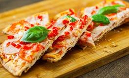 Pizza cortada con queso de la mozzarella, el jamón, los tomates, la pimienta, las especias y la albahaca fresca Pizza italiana Imagenes de archivo