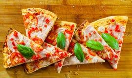 Pizza cortada con queso de la mozzarella, el jamón, los tomates, la pimienta, las especias y la albahaca fresca Pizza italiana Imagen de archivo libre de regalías