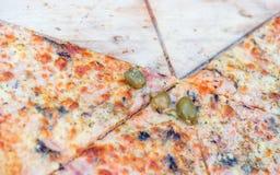 Pizza cortada en una tabla de cortar de madera Foto de archivo