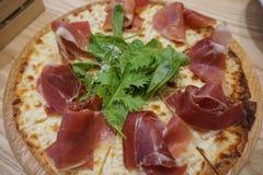 Pizza coupée en tranches avec le jambon de Parme, la fusée de salade et le parmesan sur en bois Photographie stock libre de droits