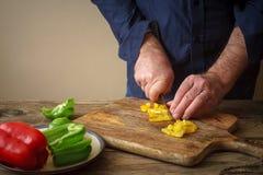 Pizza coupée en tranches de poivre sur une planche à découper Photographie stock