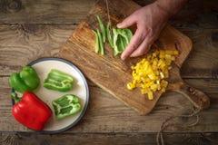 Pizza coupée en tranches de poivron vert sur une planche à découper Images stock