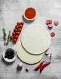 Pizza crua Massa redonda desenrolada com azeitonas, salsichas e tomates fotografia de stock