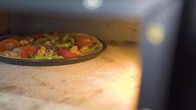 Pizza cruda con el queso, los tomates y los salchichones cocinando en horno caliente en cocina de la pizzería Hornada tradicional metrajes