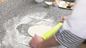 Pizza crust preparation. Chef working with dough stock footage