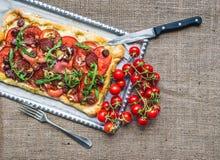 Pizza cuadrada hecha en casa con la carne, el salami, los cereza-tomates y el fre Imagen de archivo