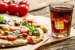 Pizza cuite au four et servi avec la boisson froide image libre de droits