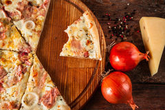 Pizza cut on slices, top view. Junk food, calories. Junk food, bad habits. Pizza sliced on rustic wooden table background. Italian traditional meal Royalty Free Stock Images