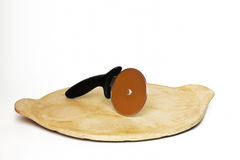 Pizza Cutter on Baking Stone. A pizza cutter standing up on a baking stone Royalty Free Stock Image