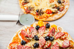 Pizza cutter together with two large pizzas with cheese olives and salami, mushrooms and tomatoes. On a wooden stand Stock Image