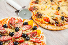 Pizza cutter together with two large pizzas with cheese olives and salami, mushrooms and tomatoes. On a wooden stand Stock Images