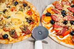 Pizza cutter together with two large pizzas with cheese olives and salami, mushrooms and tomatoes. On a wooden stand Royalty Free Stock Photography