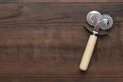 Pizza cutter on the wooden table Royalty Free Stock Photography