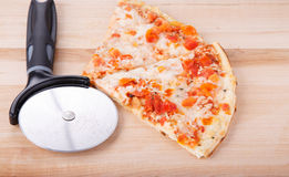 Pizza and Cutting Wheel on Wood Board Stock Images