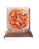 Pizza délicieuse avec du jambon et des tomates dans la boîte Images libres de droits