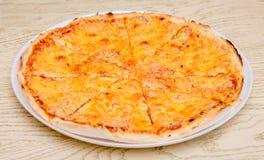 Pizza d'un plat blanc rond dans un restaurant sur un table_ en bois images libres de droits