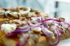 Pizza dalla fetta (pizza quadrata) - metta a fuoco sulla cipolla Fotografie Stock