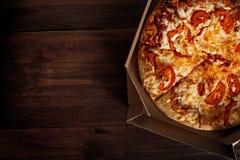 Pizza dans dans la boîte de la livraison sur le bois Photos stock