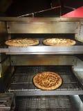 Pizza dans le four Image stock