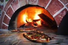 Pizza dans un four brûlant en bois Photos libres de droits