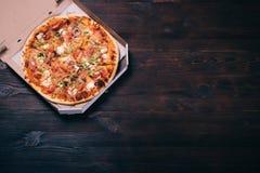 Pizza dans une boîte sur une table en bois photo stock