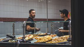 Pizza de achat d'homme la nuit à New York photo stock